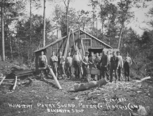 A black-and-white photograph of thirteen men posing for a group picture in front of the blacksmith shop.