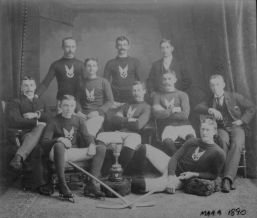 A black-and-white photograph of a group of men standing, sitting on chairs or reclining. Most are wearing the team uniform and hockey skates.