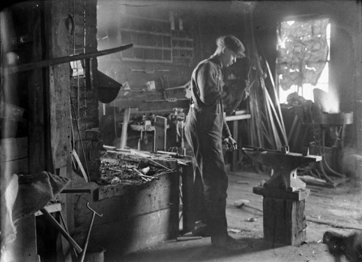 A black-and-white photograph of a man hammering a piece of metal at the Jolly Blacksmith shop.