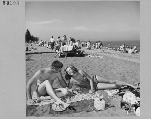 A black-and-white photograph of Kathleen Hart and Dave Phipps sunbathing on the beach.