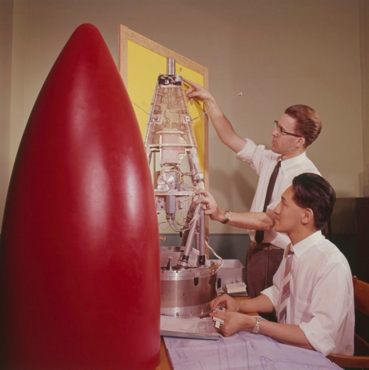 A colour photograph of the red nose cone of a rocket next to two men working on the instruments that will go inside it.