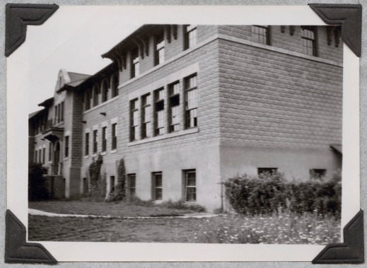 A blurry black-and-white photograph of a building taken from the side, showing the main entrance and the front of the building.