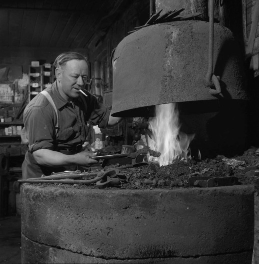 A black-and-white photograph of a man in heating a horseshoe in a forge.