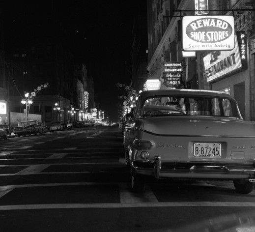 A black-and-white photograph of a street at night with cars parked on both sides and neon store signs adding light.