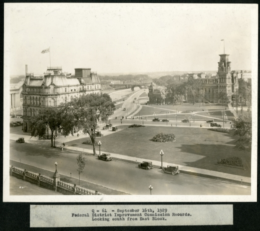 A black-and-white photograph of a quiet park and streets surrounded by two major buildings flying the Union Jack flag from their highest rooftop. Old cars are parked on the main street in the foreground.