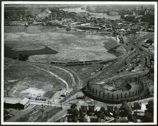 Aerial black-and-white photograph of an industrial landscape with logs floating in the water and a power station and rail lines in the foreground. The Parliamentary Precinct is in the background.