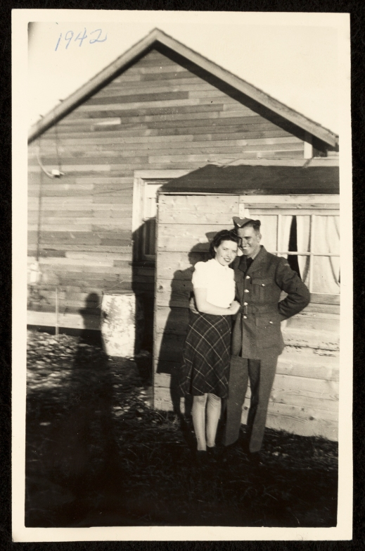 A black-and-white photograph of a man in a military uniform with his arm around a young woman wearing a flowered dress standing in front of a clapboard house.