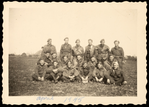 A black-and-white photograph of a group of 18 soldiers in uniform in a tilled field.