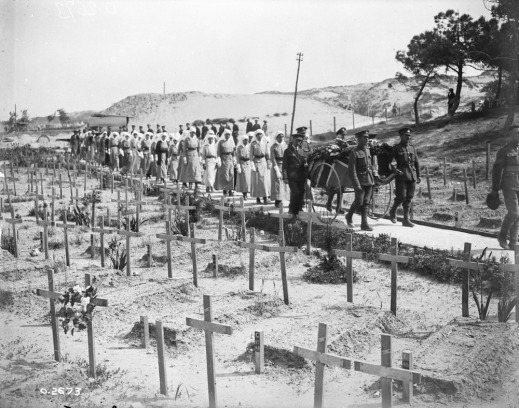 A black-and-white photograph of a funeral procession of soldiers and nursing sisters, accompanying a wheeled stretcher carrier with a flag-draped casket on it, passing through a large cemetery of temporary grave crosses.