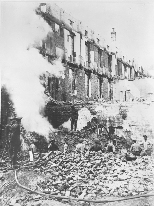 A black-and-white photograph of uniformed soldiers working amidst the rubble of a large, heavily damaged brick building that has been bombed.