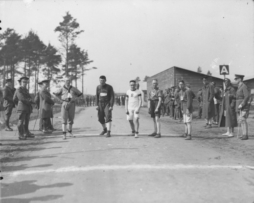 A black-and-white photograph of five men lined up on a road ready to start a race. Soldiers stand and watch from both sides of the road.