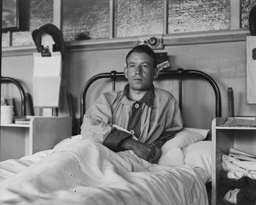 A black-and-white photograph of a patient in convalescent uniform reclining in a hospital bed.
