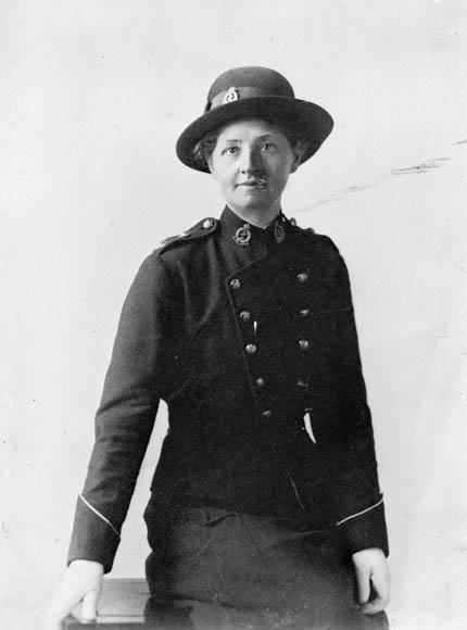 A black-and-white studio portrait of a nursing sister, in her uniform and hat, leaning against a table.
