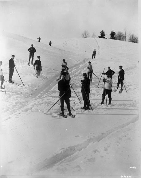 A black-and-white photograph of people skiing.