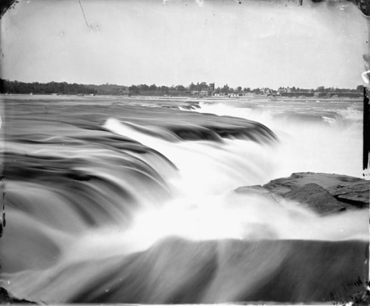 A black-and-white close-up photograph of Chaudière Falls with buildings visible on the distant shore.
