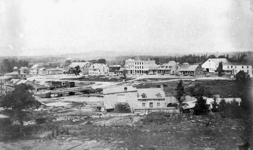 A black-and-white photograph of a sparsely settled town with a few buildings in the background.