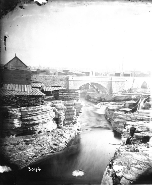 A black-and-white photograph of an industrialized river landscape showing a bridge, striated rock and buildings in the background.