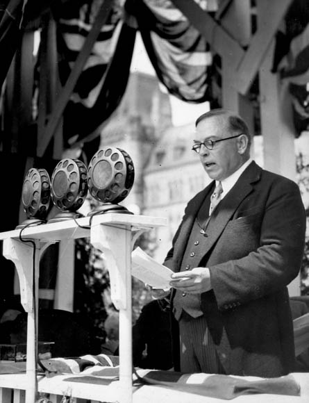 Black-and-white photograph of the Right Honourable William Lyon Mackenzie King, Prime Minister of Canada, speaking at the dedication of the Peace Tower carillon.