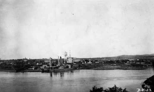 A black-and-white photograph of a river shoreline where a manufacturing complex is situated. A large church is located up on the hill behind it.