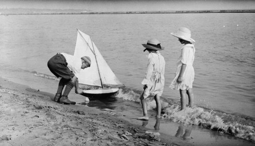 A black-and-white photograph of two girls watching a boy launch a model yacht into the water.