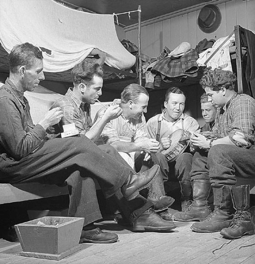 A black-and-white photograph of a group of men sitting around in a bunkroom playing music and smoking.