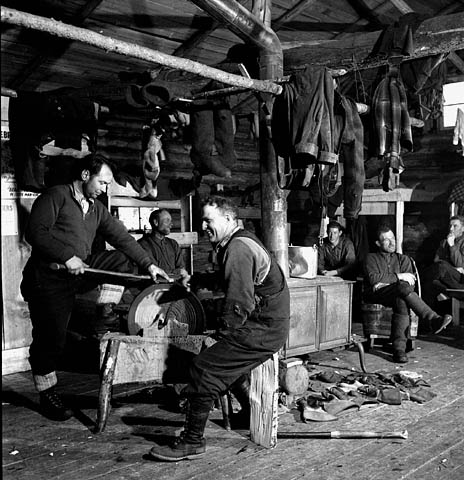 A black-and-white photograph of men relaxing and sharpening their axes in a log bunkhouse.