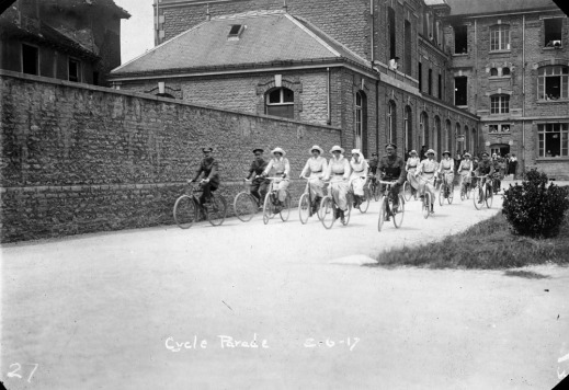 "A black-and-white photograph of uniformed men and women riding bicycles. The women are dressed in light-coloured uniforms with dark belts and hats, while the men wear khaki uniforms with hats. They pedal along a pathway that is bordered on the left by a tall brick wall. A large building with windowed façades is prominent in the background. The caption, ""Cycle Parade"" is written on the lower half of the image."