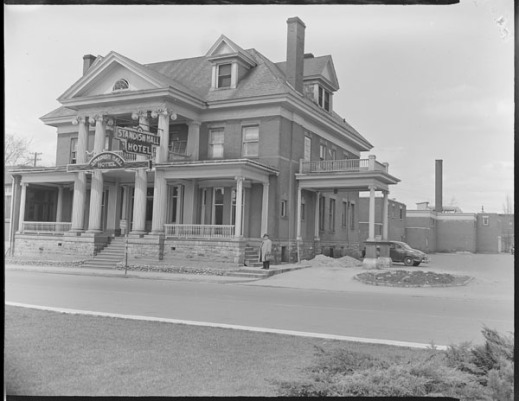 """A black-and-white photograph of a large building, with a wide veranda and a sign reading """"Standish Hall Hotel."""""""
