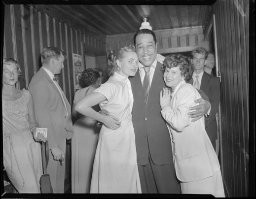 A black-and-white photograph of Duke Ellington standing between two women at the Standish Hall Hotel and posing for a picture.