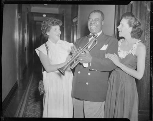 A black-and-white photograph of two women with a man holding a trumpet.