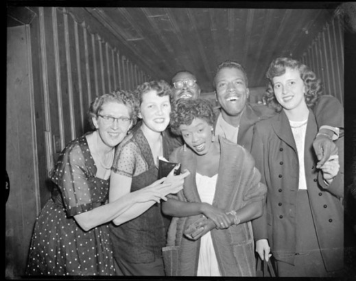 A black-and-white photograph of five young people gathered around American jazz singer Sarah Vaughan to have their picture taken.