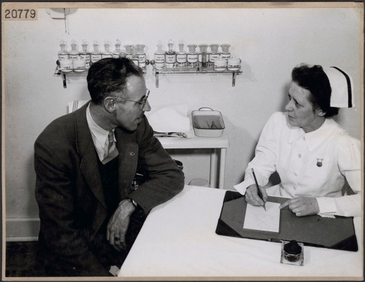 A black-and-white photograph of a nurse speaking with a man in a medical office and taking notes.