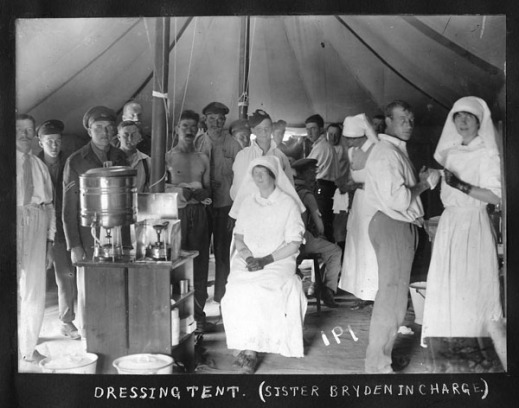 A black-and-white photograph shows nursing sisters dressed in white aprons and veils, attending to a crowd of male patients inside a tent. One of the nursing sisters is sitting on a chair, with her feet and hands folded, staring at the camera. The other two nursing sisters are standing as they bandage the wounds of soldiers. The patients are dressed in casual clothing and some are in uniform. Medical supplies including bandages and pails are seen in the foreground and mid-ground.