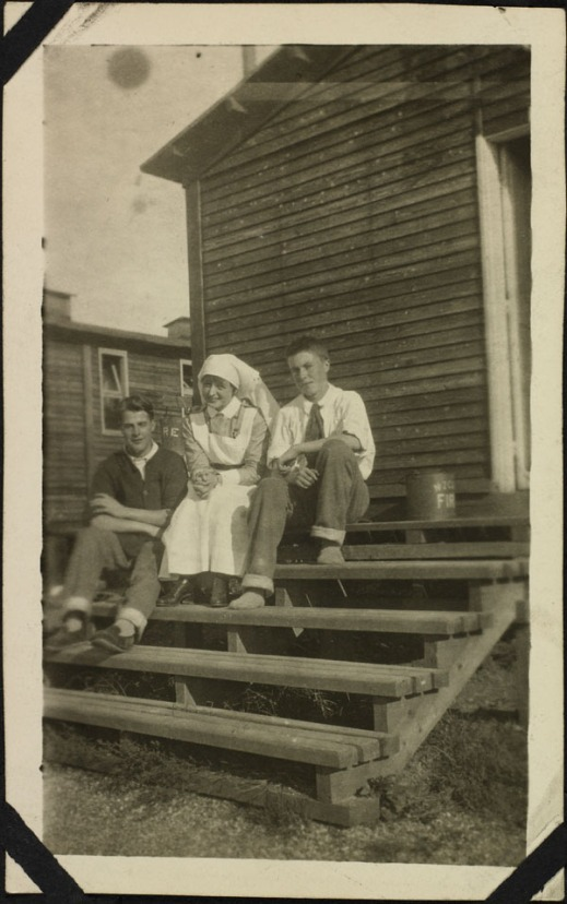 A black-and-white photograph showing three people sitting on the steps of a wooden hut. Two men, wearing trousers with rolled up legs and casual shirts, sit on either side of a uniformed nurse. All are smiling at the camera.
