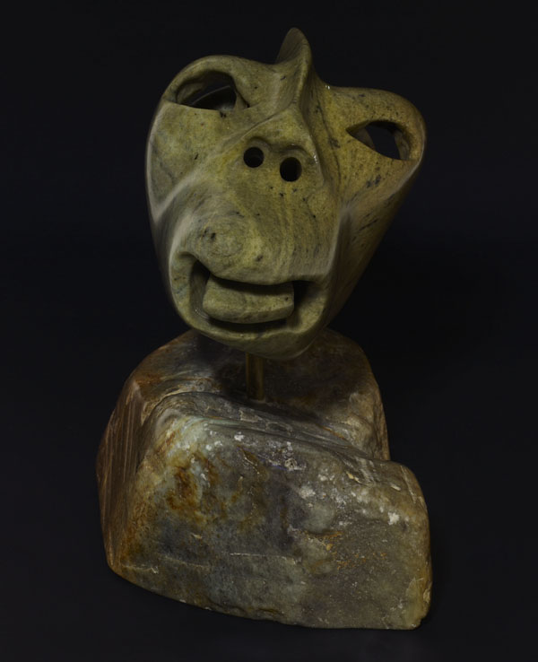 A colour photograph of the front of a stylized sculpture of a man with his tongue sticking out.