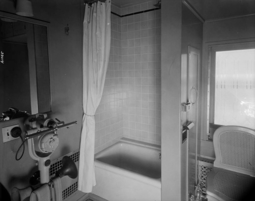A black-and-white photograph of a shower, bath and toilet in a train lounge car.