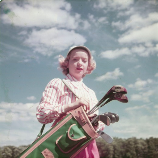 A colour photograph of a woman carrying her golf clubs under a partially clouded blue sky.