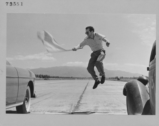 A black-and-white photograph of a man jumping up into the air between two cars, and waving a flag to start a race.