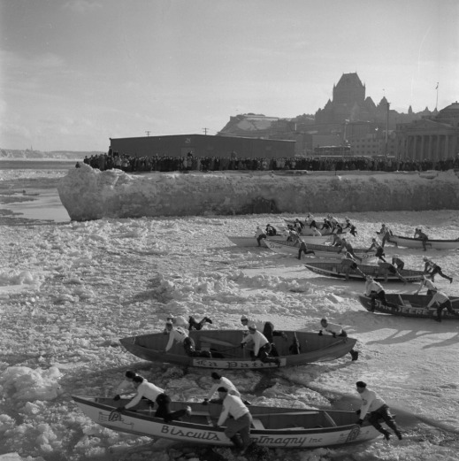 A black-and-white photograph of eight teams pushing their canoes on from the frozen portions of a river toward open water.