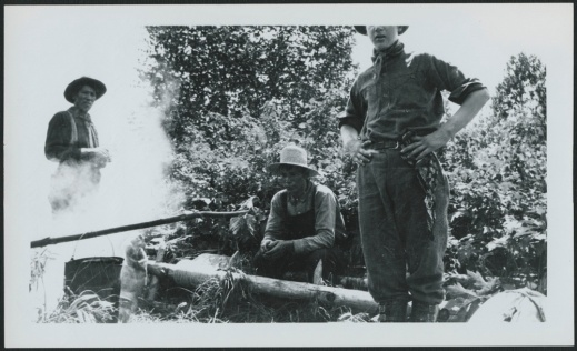 A black-and-white photograph of three men gathered around a fire, presumably having a midday food break.
