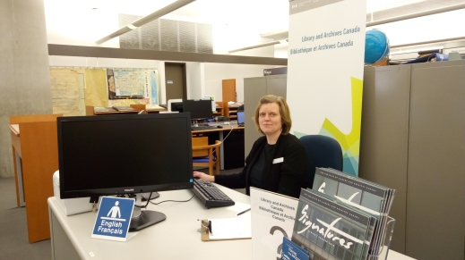A colour photograph of a woman sitting behind a service desk with a Library and Archives Canada banner behind her.