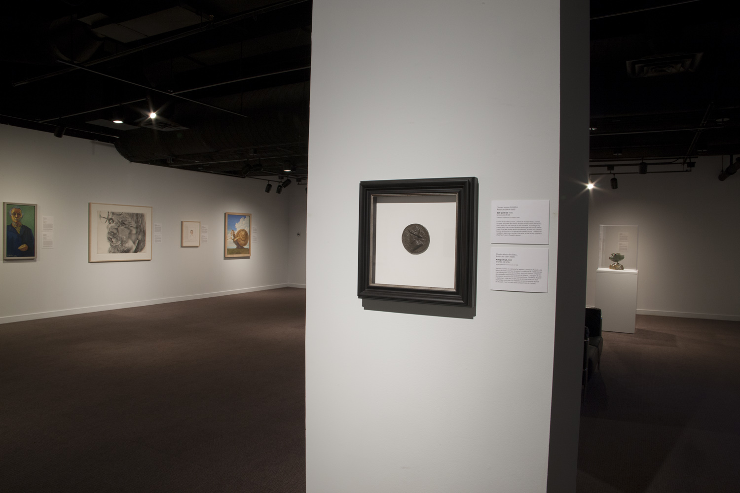 A colour photograph of a dimly lit room with various art pieces hung on the walls.