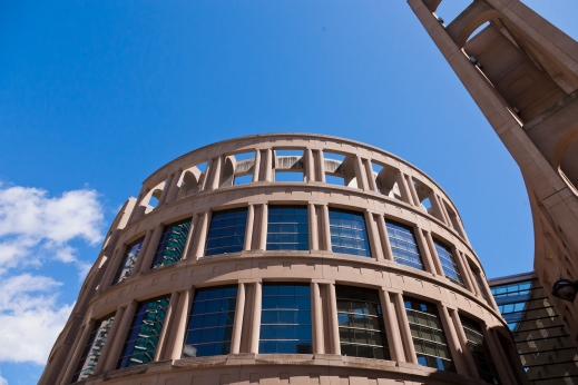 A colour photograph of a round building resembling the architecture of the Colosseum in Rome but clearly contemporary with its glass windows on the top two floors.