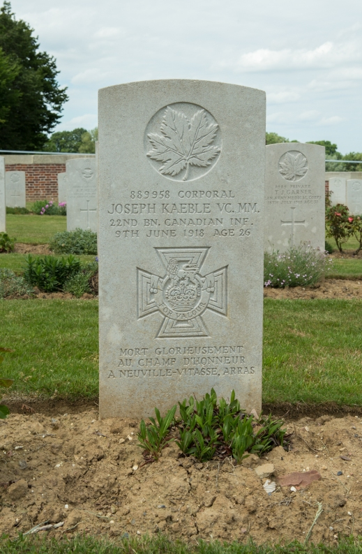 A colour photograph of a gravestone with some plants beginning to grow. In the background are other graves.