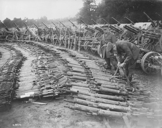A black-and-white photograph of hundreds of guns, rifles, and machine guns of varying sizes laying on the ground. A soldier stands examining the guns, and a second soldier bends over examining the strap of a gun.