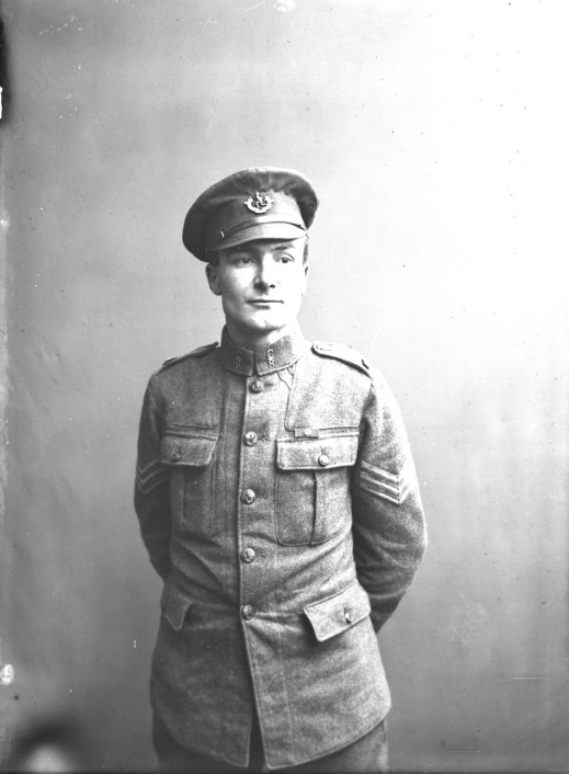 A black-and-white photograph of a soldier in full uniform standing with his hands behind his back.