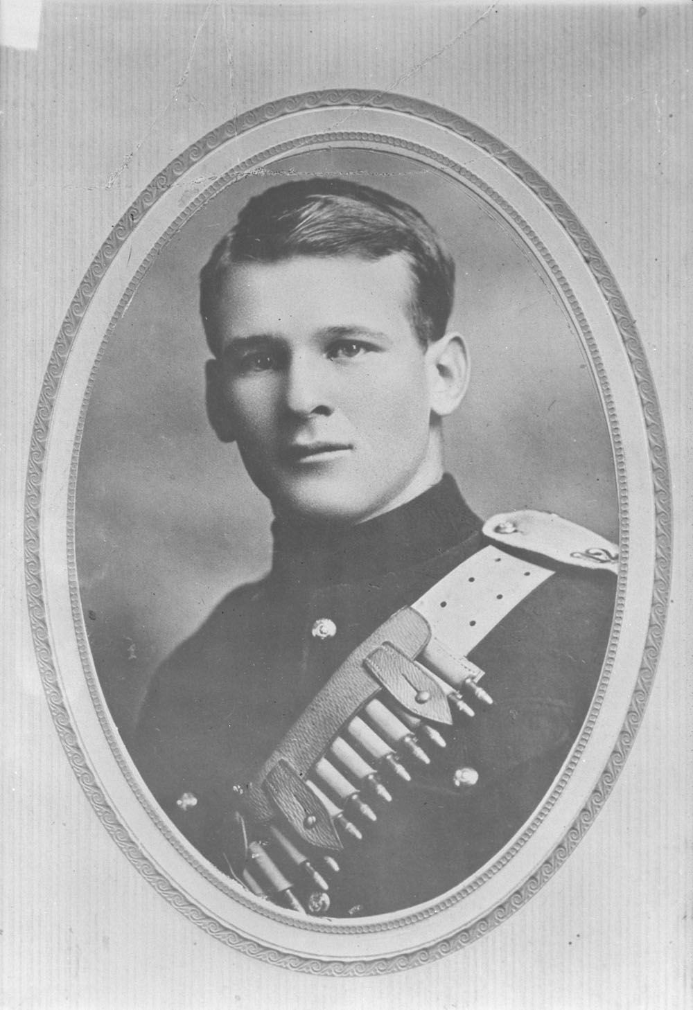 A black-and-white bust photograph of a soldier wearing a light coloured non-commissioned officer (NCO) belt with bullets across his chest.