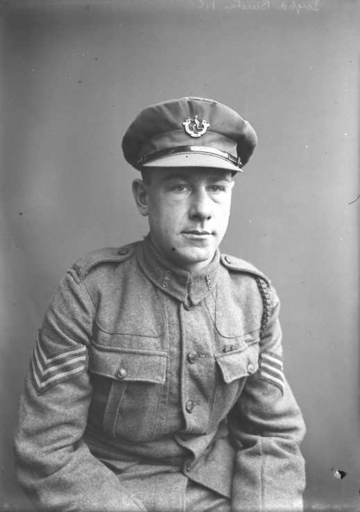 A black-and-white photograph of a seated soldier in uniform and cap.