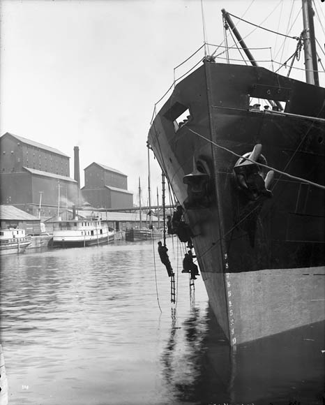 A black-and-white photograph of a ship moored to the dock. Four men are working from ladders hanging off the bow.