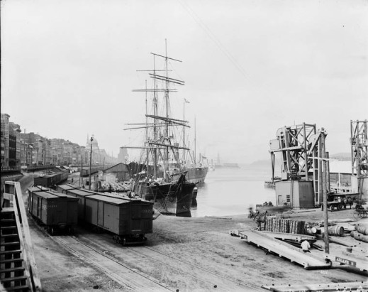 A black-and-white photograph of railway lines running along a ship-lined harbour front.